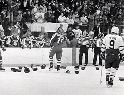 Referee and players on hat-littered ice