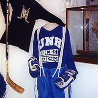 UNH Hockey uniform, stick, and sweatshirt