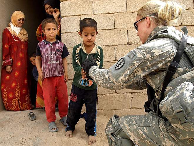 female soldier handing something to child