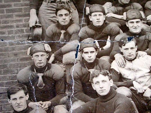 A football team photo in which they have nose-guards hanging from their necks