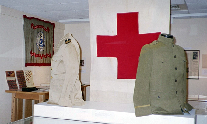 Photo of exhibit includes military uniforms and a red cross banner