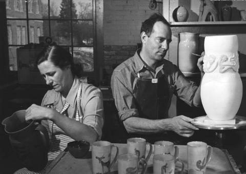 black and white photo of woman and man making pottery in a studio